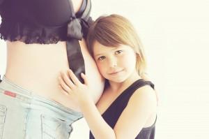 Dziesko przytulone do brzycha mamy w ciąży